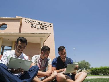 Titulados de la UJA con un portátil en los exteriores del Campus