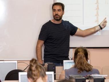 Un profesor señala la pizarra electrónica durante una clase